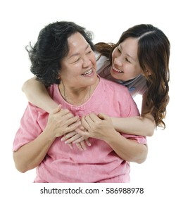 Portrait of Asian adult daughter embracing senior mother and smiling, isolated on white background.