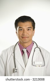 Portrait of Asian American male doctor against white background.