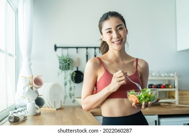 Portrait of Asian attractive woman hold salad bowl and look at camera. Beautiful sport girl in sportswear enjoy eat clean vegetables after exercise for health in house. Diet and Healthy food concept. - Shutterstock ID 2022060287