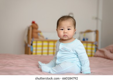 Portrait of asian baby  boy little 7 months old on the bed in his room
