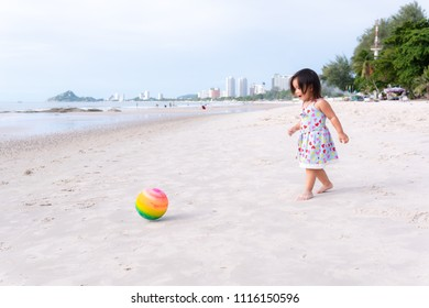 Portrait of Asian baby girl playing ball on beach at Hua Hin, Thailand