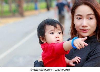 Portrait of asian baby girl are pointing something to young mother. While walking in the park