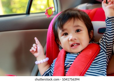 Portrait of Asian baby girl was smiling happily and sit in the red car seat for safety.while parents are going to travel