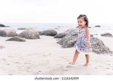 Portrait of Asian baby girl walking on beach at Hua Hin, Thailand