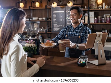 Portrait of asian barista hold take away coffee and Croissant cup and serving to customer in cafe with other barista working in background