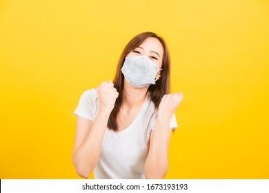Portrait Asiatische schöne junge Frau mit Gesichtsmaske schützt Filterstaub pm2.5, Virus- und Luftverschmutzung ihr die Hände froh aufgeregt, nachdem sie sich von der Krankheit auf gelbem Hintergrund erholt hat