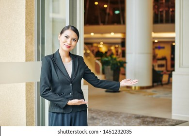 Portrait of Asian beautiful manager in formal wear standing near the entrance and inviting you to the hotel