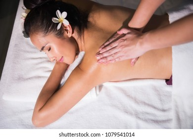 portrait of Asian beautiful tan woman with white Plumeria in spa club. Body care treatment by Thai oil. Cute girl having back spiral massage by professional massager hands on bed.