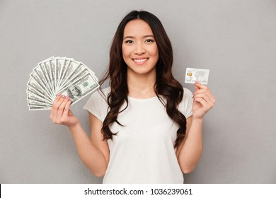 Portrait of asian beautiful woman 20s holding fan of money dollar banknotes and credit card isolated over gray background
