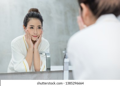 Portrait of asian beautiful woman watch mirror cleansing face in the morning before shower. Young girl washing face with clean water applying cream with her hand. Healthcare lifestyle hygienic concept