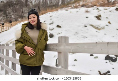 Portrait of an asian beautiful woman wearing green coat and wool hat, standing and posing