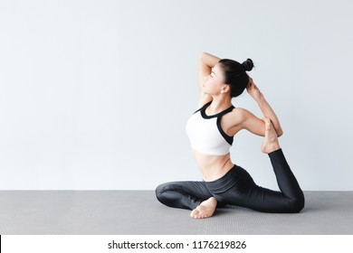 Portrait of asian beautiful young woman wearing sportswear practicing yoga in studio,natural light.Concept : yoga poses for beginner. Mermaid Pose.(Eka Pada Raja Kapotasana variation)
