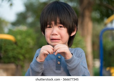 Portrait of asian boy  crying in the park