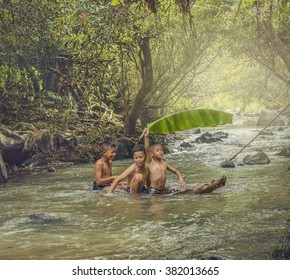 Portrait of Asian boy fisherman with waterfall in outdoors,Children fishing in the river,The boys are enjoying playing the stream