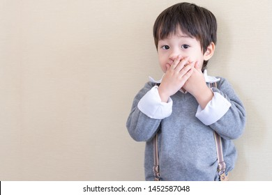 Portrait asian boy standing and used two hands closed his mouth and looking to camera on cream color background