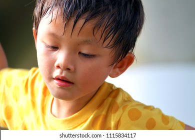 The portrait of an asian boy (Taiwanese) concentrates on his sport with seriously facial expression and sweat on his forehead.