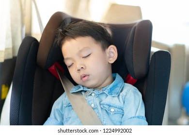 Portrait of asian boy wearing jean shirt sleeping in car seat, image with toning and effect of soft shining sun