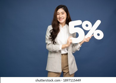 Portrait of Asian business woman showing and holding 5% number or five percent isolated over deep blue background