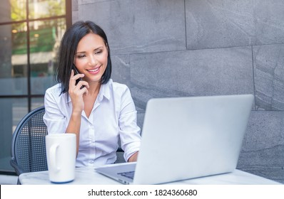 Portrait of asian business woman talk on smartphone using notebook laptop at coffee cafe outdoors. Beautiful girl at desk computer online business. Startup business asia woman, sme telemarketing.