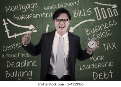 Portrait of asian businessman angry holding hammer and alarm with scribble on the chalkboard