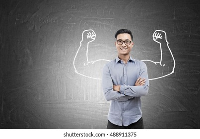 Portrait of Asian businessman in glasses standing near blackboard with muscular hands sketch on it. Concept of intellectual power. Mock up