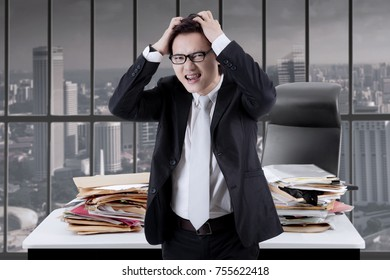 Portrait of Asian businessman looks stressful while standing near the window with paperwork on the desk