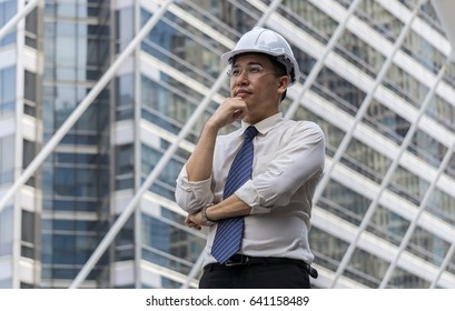 Portrait of asian businessman stand at sidewalk in the city and dreaming of success.