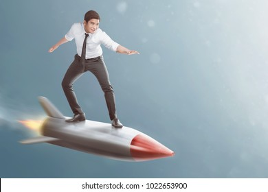 Portrait of asian businessman standing on flying rocket on the sky background