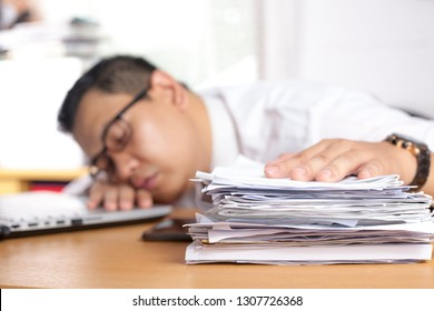 Portrait of Asian businessman tired for overworked and sleep in front of his laptop and paperworks at the office