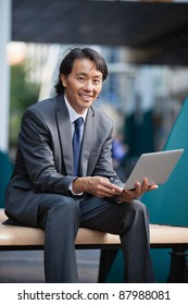 Portrait of an Asian businessman using laptop