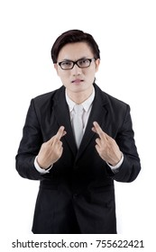 Portrait of Asian businessman wearing a formal suit while crossing his finger, isolated on white background