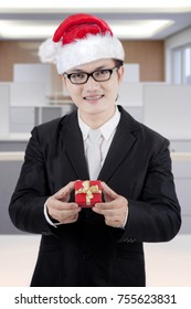 Portrait of Asian businessman wearing Santa hat while holding a Christmas gift and standing in the office
