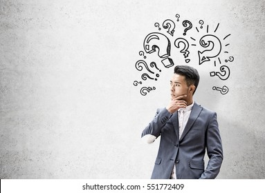 Portrait of an Asian businessman who is thinking and solving a problem while standing near a concrete wall with question mark sketches. Mock up