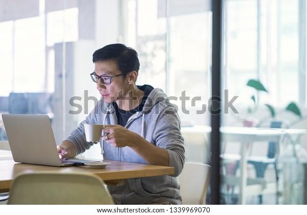 Portrait of Asian businessman working on laptop in office