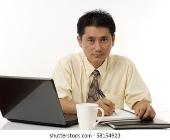 Portrait of Asian businessman writing at his desk