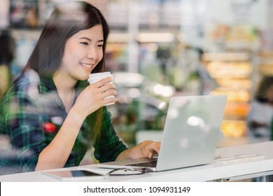 Portrait of asian businesswoman in casual suit drinking and working with technology laptop in happiness action at the desk beside the glass in modern office, Business owner and entrepreneur concept