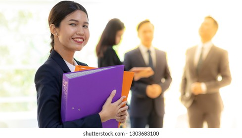Portrait of Asian Businesswoman hold working file with business team in background using for coporate background work, panoramic web banner composition
