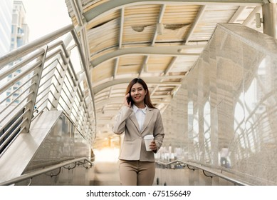 Portrait of Asian Businesswoman talking on smartphone, holding on cup of coffee and walking by the way of modern office. Business and People Concept.