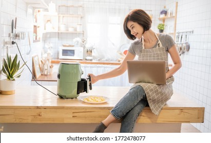 Portrait of asian chef girl cooking potato fried by Air Fryer machine in kitchen home. New normal work at home lifestyle. Technology eco friendly home smart device, asian housewife concept
