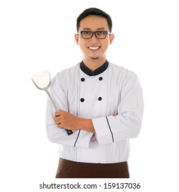 Portrait of Asian chef holding spatula, smiling and standing isolated on white background.