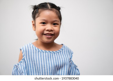 Portrait of Asian child 5 year old and to collect hair and a big smile on isolated white background, She is Happiness, radiance in youth