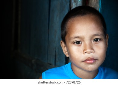 Portrait of an Asian child - Filipino boy by wall in natural light