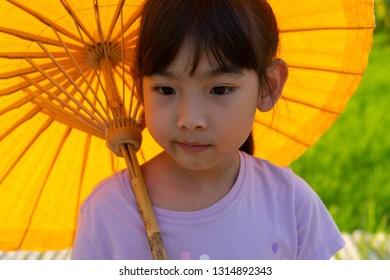 Portrait Asian child girl hold Umbrella Walk on a wooden bridge