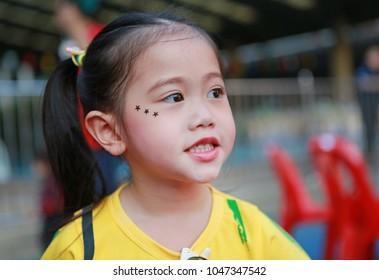 Portrait of Asian child girl with makeup and sticking on face sequins in the form of stars.