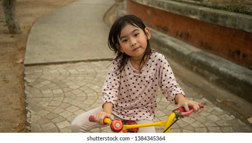 Portrait Asian child girl Riding a bicycle playing in the garden