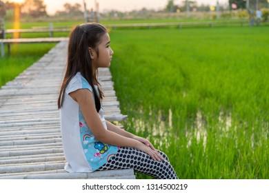 Portrait Asian child girl Sit on a wooden bridge