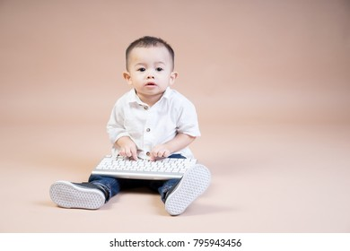 Portrait of an Asian child holding a keyboard on a brown background. Concept of nurturing kids with technology at an early age.