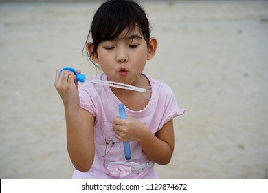 Portrait Asian child little girl Blow bubbles Sea background