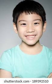 Portrait Of asian child smile on his face, on gray background .