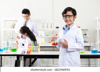 Portrait asian child student boy holding glass beaker in laboratory classroom